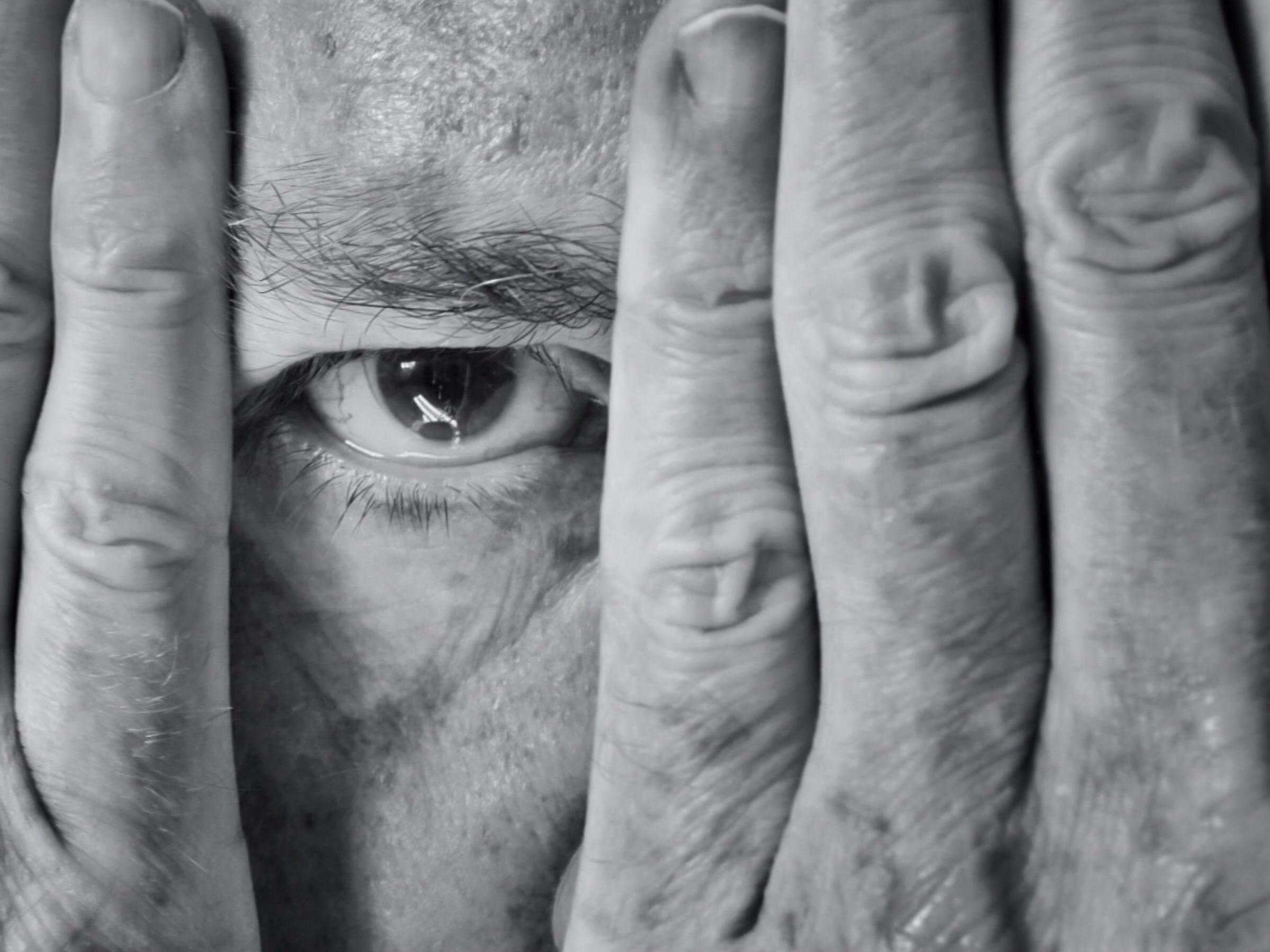 man looking thru fingers shutterstock_157833014